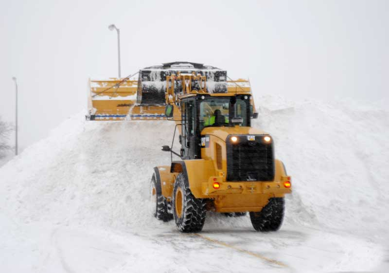 a snow plus front end loader stacking snow in a commercial parking lot in chicago il